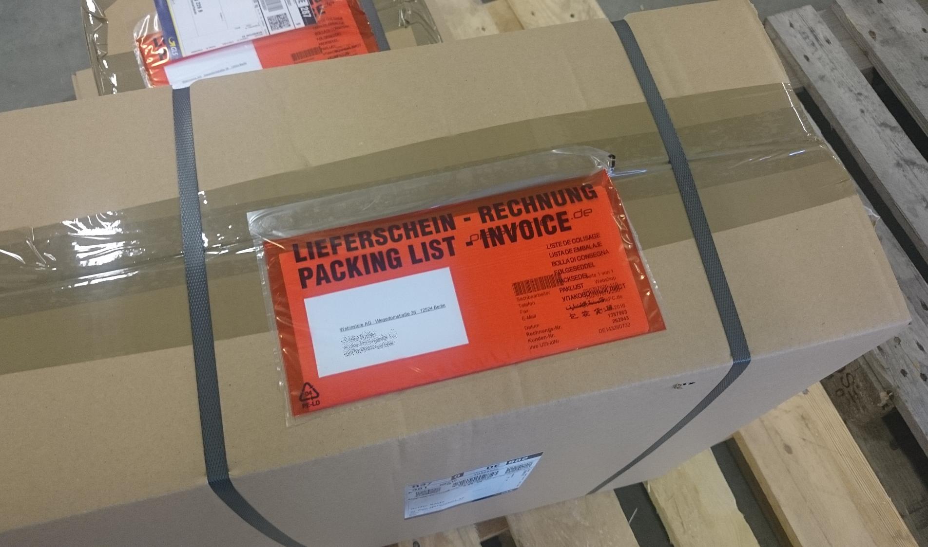 Rechnung in der roten Versandtasche am Paket